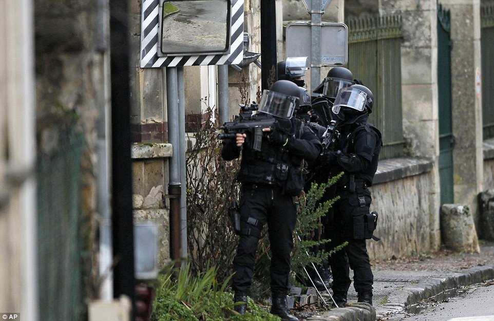 Training their weapons: Terror police scour the village of Longpont after the suspects abandoned their car and fled on foot into nearby woods