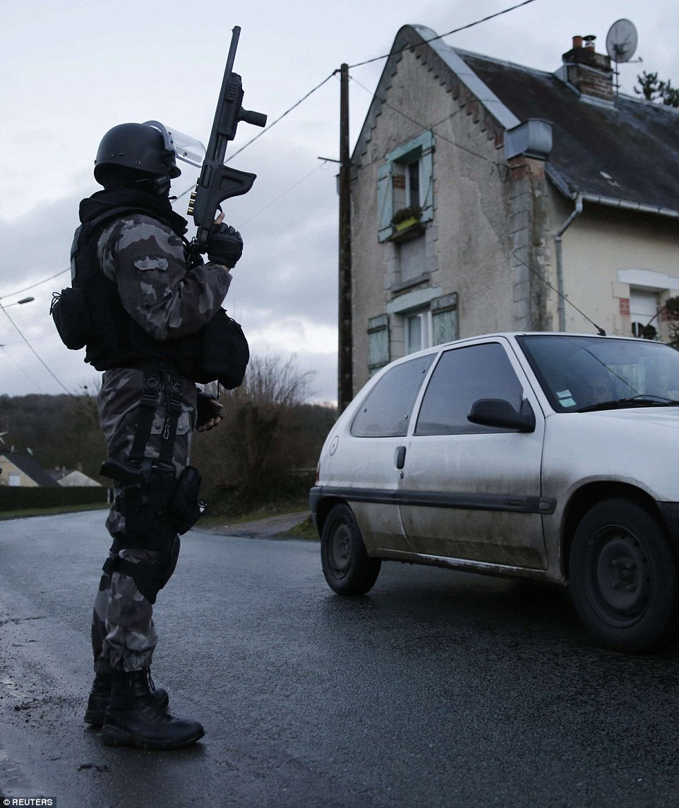 On the lookout: A member of the French GIPN intervention police forces secures a neighbourhood in Corcy, north-east of Paris