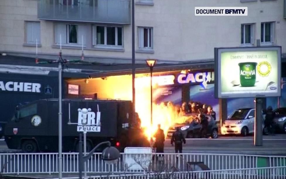 An explosion lights the front of a kosher supermarket as French police special forces launch their assault, where several people were taken hostage in eastern Paris